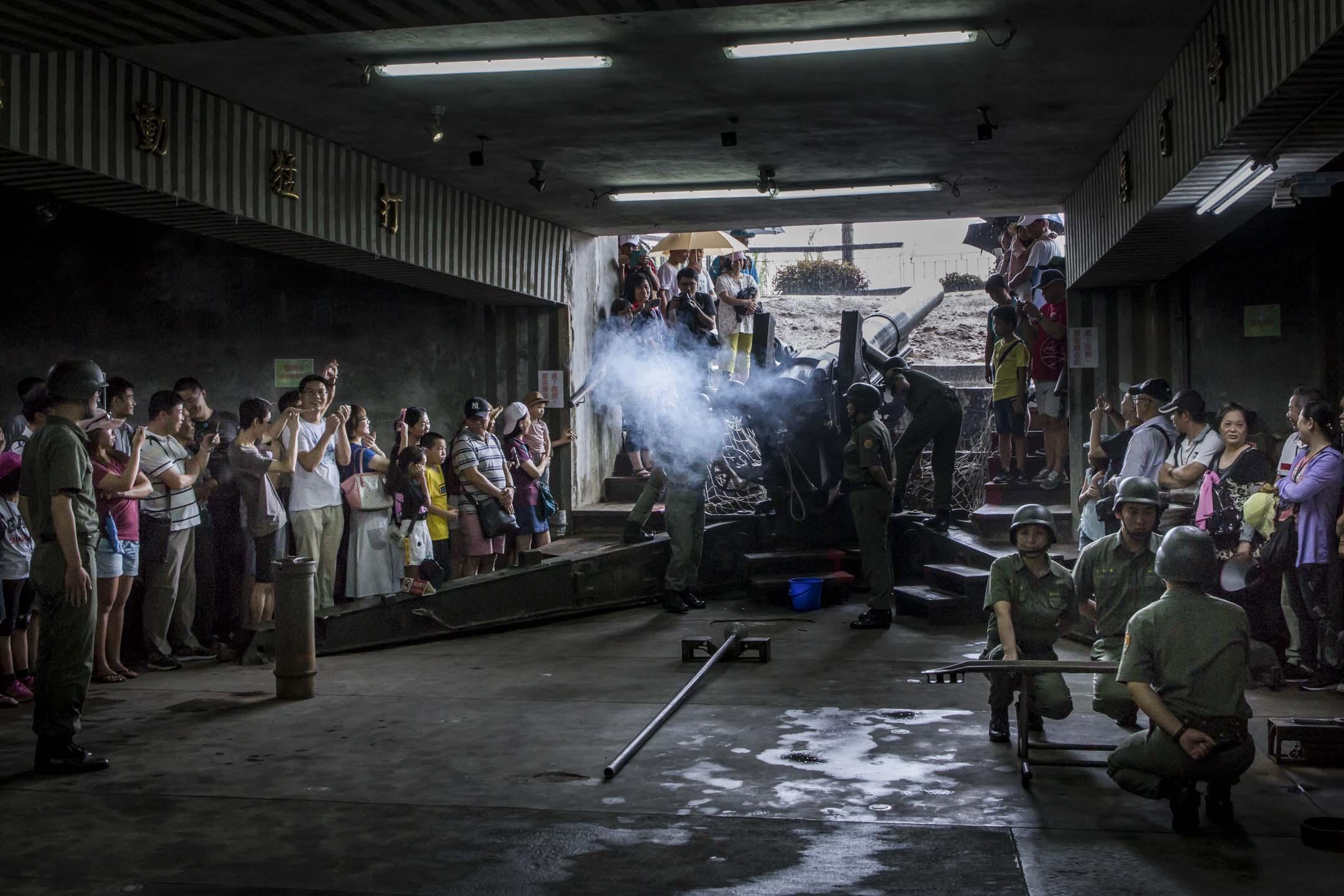 2018年8月19日,旅客在金門獅山砲陣地觀看工作人員表演砲彈射擊。 攝:陳焯煇/端傳媒