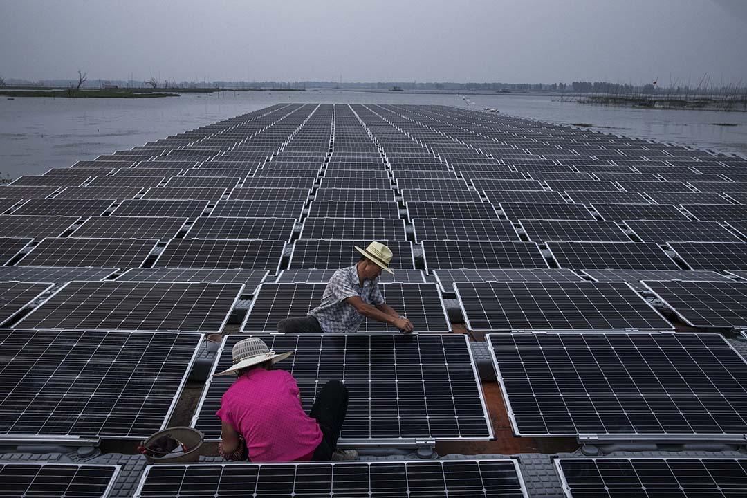 中國近年大力投資可再生能源,在2000年代起就把可持續發展和生態保護等概念納入國家能源白皮書和投資方針。圖為2017年6月12日,安徽淮南,中國工人正在建設大型的太陽能板。