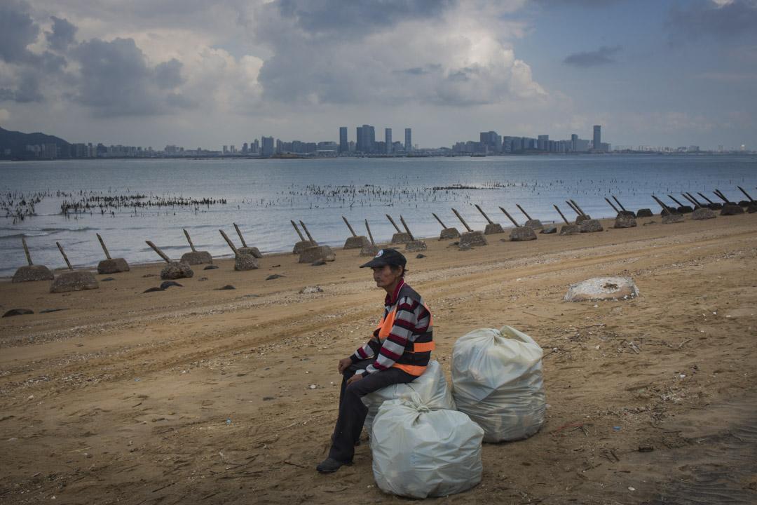 2018年8月20日,小金門海灘上佈滿軌條砦,一名海灘工作人員正在歇息,對岸為中國廈門市。
