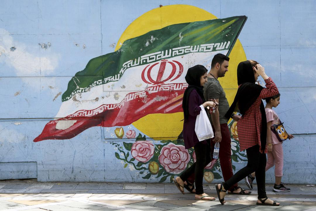 伊朗人傾向於短期利益考量,善變和言不由衷,以在不斷變化的外部形勢中生存。這次面對美國製裁和暗淡的經濟前景,伊朗人大抵又嗅到了「大難將至」的味道,開始了末日前的狂歡。2018年8月,伊朗人走過街上壁畫,繼續日常生活。 攝:Imagine China