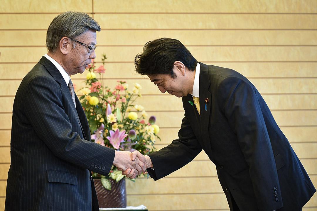面對日本政府長久無視沖繩民意,執意在邊野古建設新美軍基地的傲慢態度,最終促使翁長於2014年決定出馬參加當年的縣知事選舉。 圖為2015年4月17日,翁長雄志與日本首相安倍晉三會面。