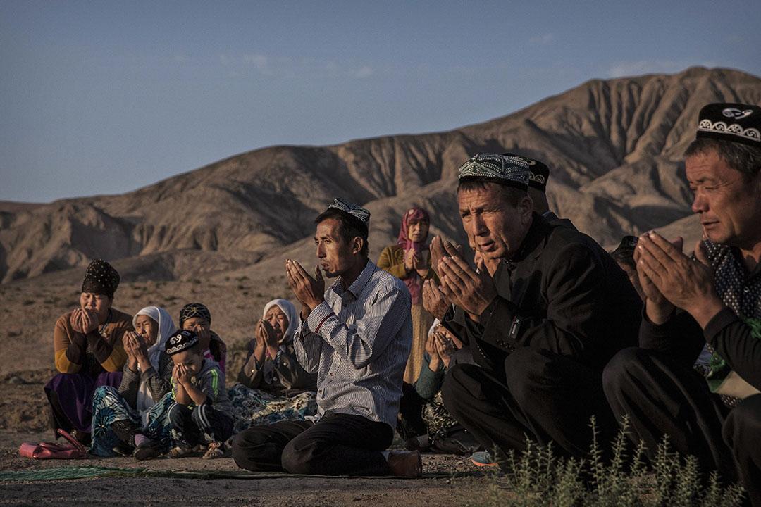 """據美國官員和聯合國專家稱,多達100萬人現在被關押在一個不斷擴大的「政治再教育」營地網絡中,這大約相當於中國新疆地區穆斯林人口的7%。 圖為2016年9月12日,新疆省吐魯番縣的寺廟,一個維吾爾家庭在""""開齋節""""的早晨祈禱。 攝:Kevin Frayer/Getty Images"""