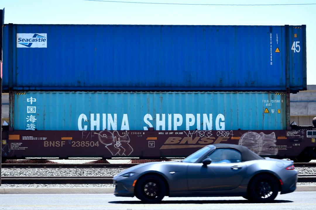 2018年7月12日,美國加州長灘,一輛車駛過中國海運集團集裝箱。 攝:Frederic J. Brown/Getty Images