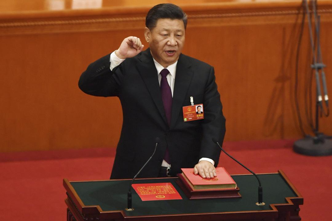 2018年3月17日,國家主席習近平用手按着他推動修改的新憲法,宣誓就職。