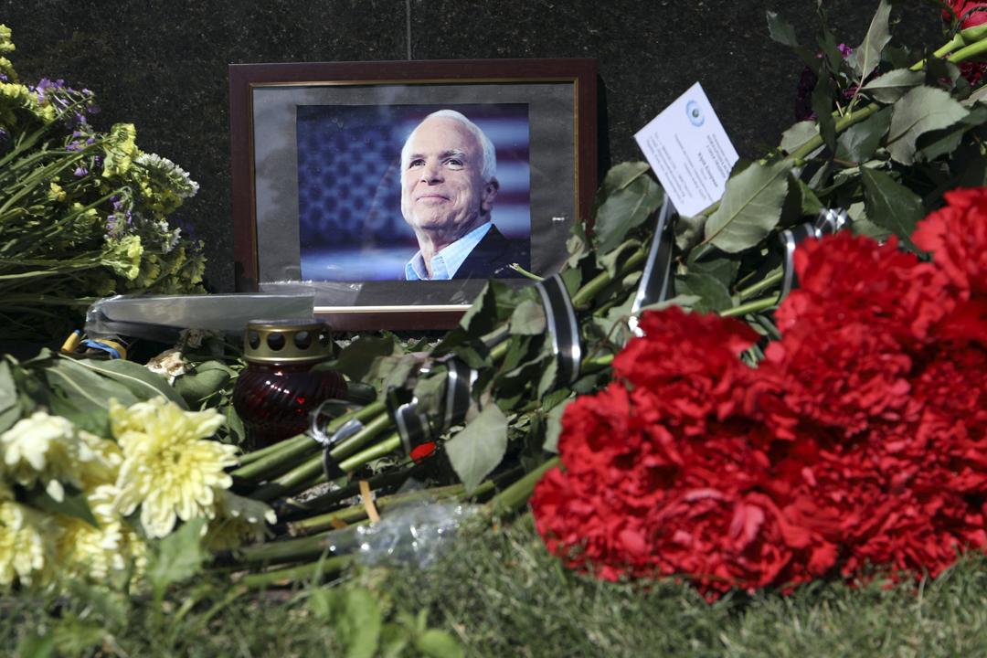 2018年8月27日,美國駐烏克蘭大使館外,有民眾擺放麥凱恩(John McCain)的遺照並獻上鮮花致敬。 圖片來源:東方 IC