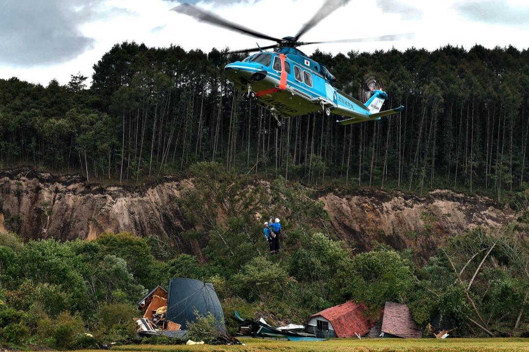 2018年9月6日,日本北海道厚真町,搜救人員從瓦礫中拯救一名男子,用直升機送離現場。