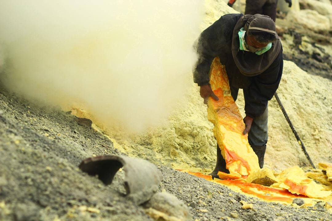 工人正收集已凝固變冷的硫磺。