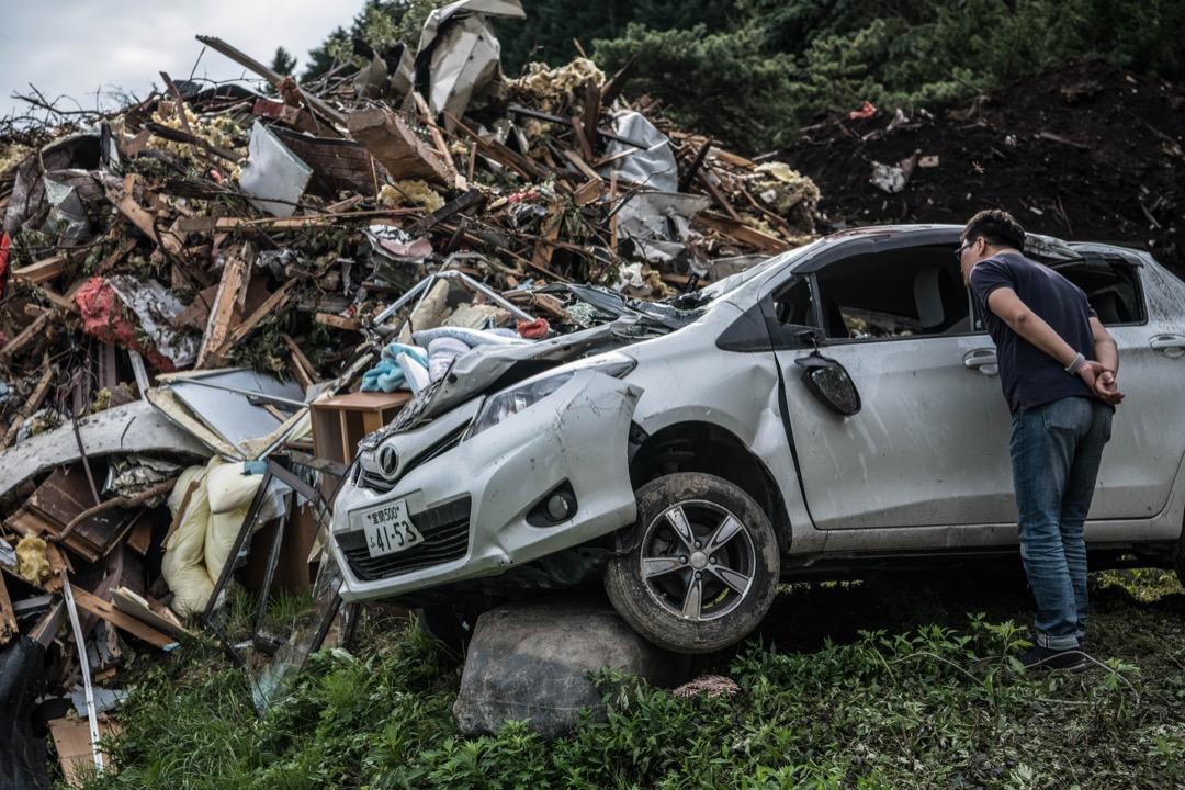 2018年9月8日,日本北海道厚真町,地震引發山泥傾瀉,壓毀多間房屋及多輛汽車,一名途人走到汽車前看汽車的損毀情況。