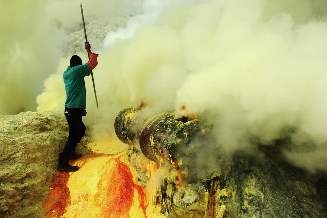 工人們在火山和湖邊通過陶瓷管引出液體的硫磺,然後以人工點火方式凝固硫磺。 攝:Muhammad Fauzy Cahniago/Sijori Images/ Caters News via Imagine China