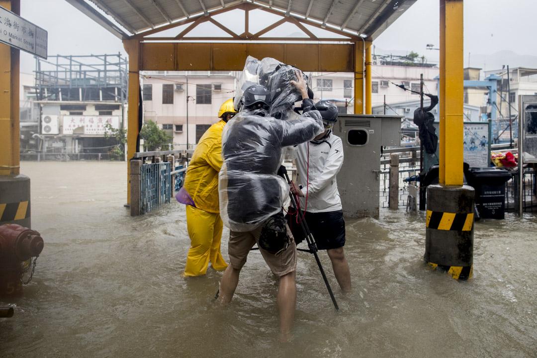 2018年9月16日,颱風「山竹」襲港的十號風球下,電視台記者在大澳錄制新聞期間忽然遇到強風,記者和攝影師合力扶著攝錄機。 攝:Stanley Leung/端傳媒