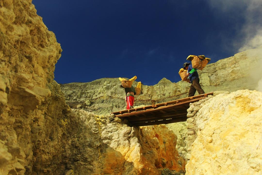 硫磺工人背著兩籃已冷卻的硫磺,走過險要的木橋。