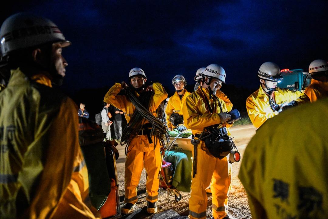 2018年9月7日,日本北海道厚真町,地震引發山泥傾瀉,導致多間房屋倒塌壓毀,搜救人員在晚上準備到瓦礫中搜救倖存者。