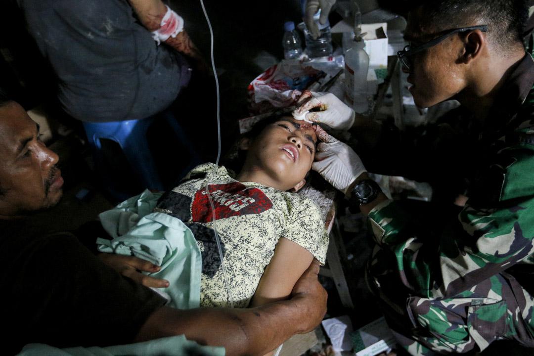 2018年9月29日,地震幸存者在軍事醫院外接受治療。