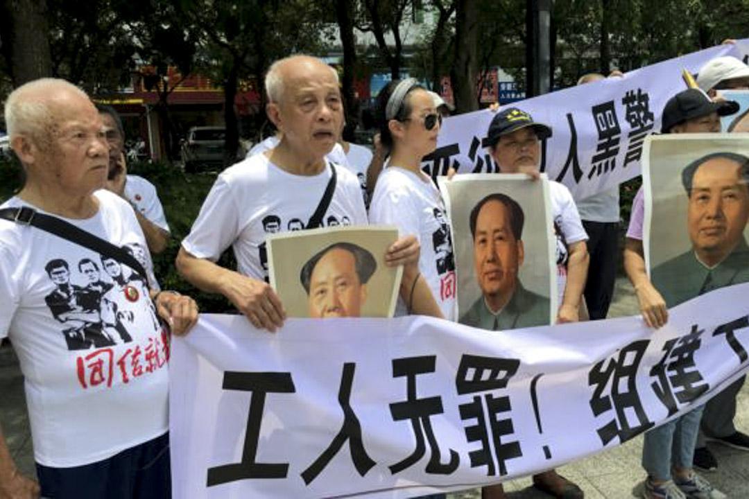 2018年8月6日,市民在中國廣東省深圳市坪山區燕子嶺派出所外示威,手持標語及毛澤東肖像,支持佳士工廠工人。