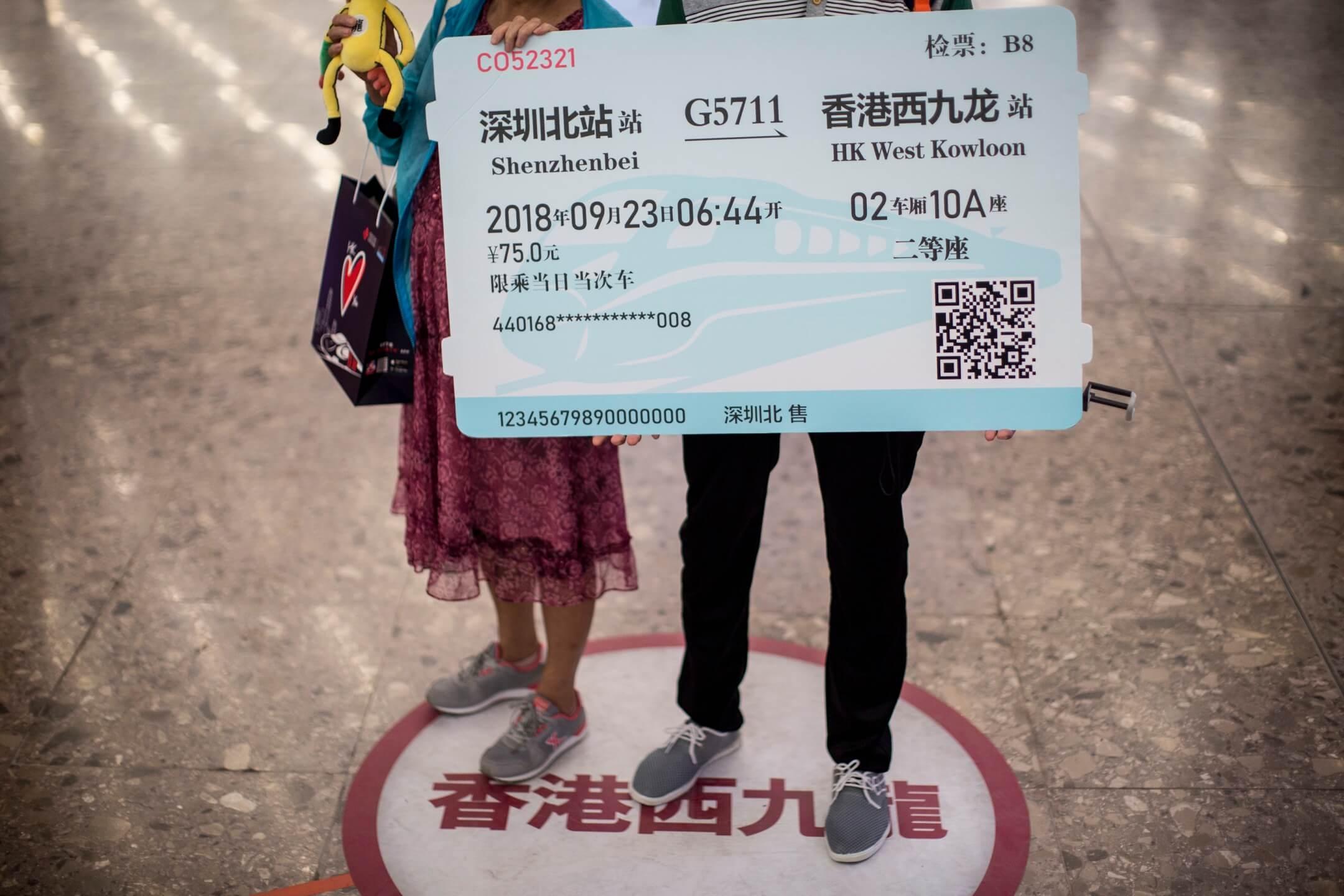香港西九龍高鐵站入境大堂,兩名內地旅客拿著道具車票拍照。