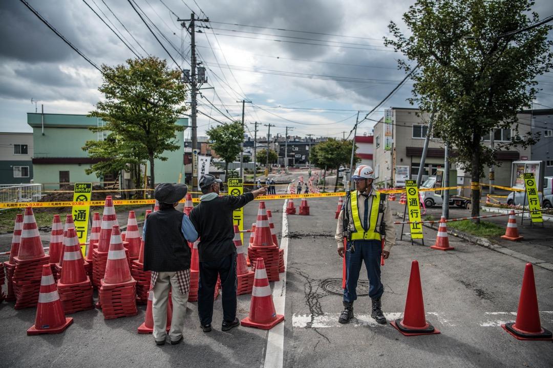 2018年9月8日,日本札幌清田區,道路在地震中嚴重損毀,需封閉進行維修,有道路工人在封鎖線引導市民到安全地方,兩名途人遠觀室內的損毀情況。