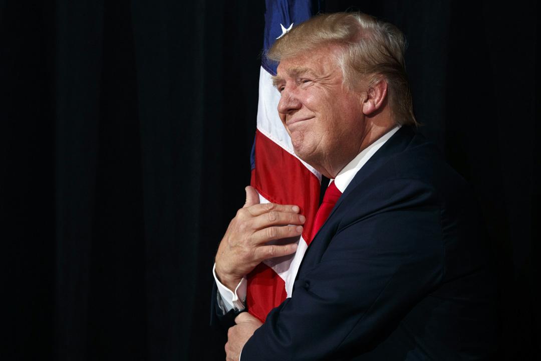 特朗普當選,代表了美國「白種怒漢」對過去幾十年種族平權的反抗,也代表了美國勞工階級對三十年來全球化的反擊。從這個意義來說,特朗普施政體現了時代的斷裂。圖為2016年10月24日,特朗普在競選集會上擁抱美國國旗。