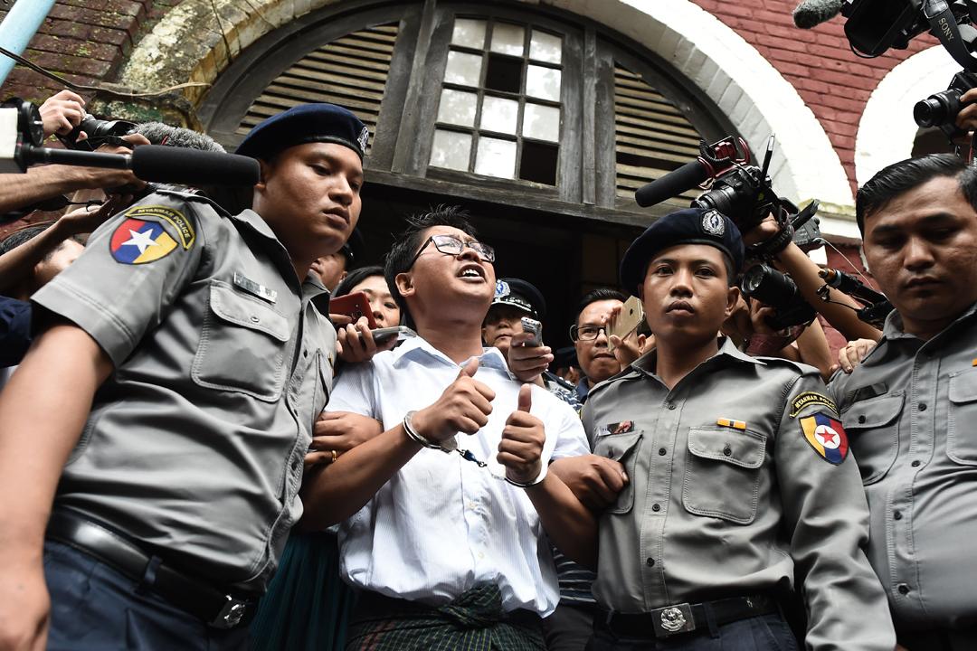 2018年9月3日,仰光法庭裁定記者瓦倫(Wa Lone)及吳覺梭(Kyaw Soe Oo)違反《政府機密法》,分別判處兩人監禁七年。圖為瓦倫被警員押送離開法庭時,對在場支持者及傳媒高喊自己無罪。 攝:Ye Aung Thu / AFP / Getty Images