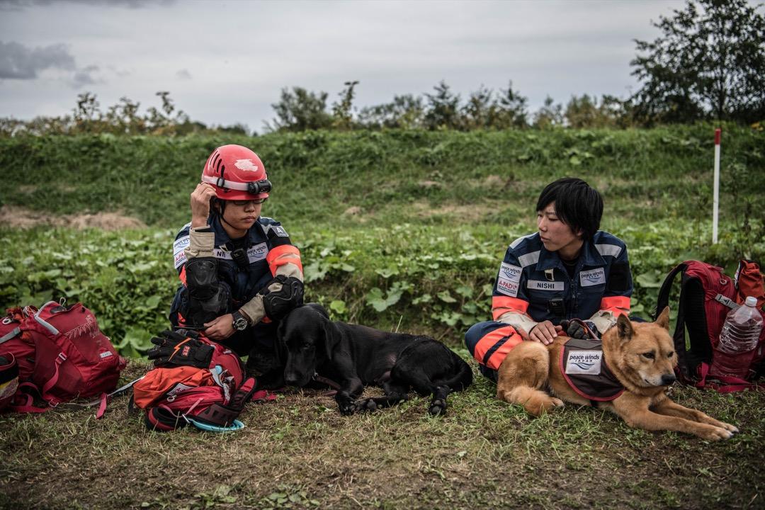2018年9月8日,日本北海道厚真町,搜救人員與搜索犬在災場附近休息。