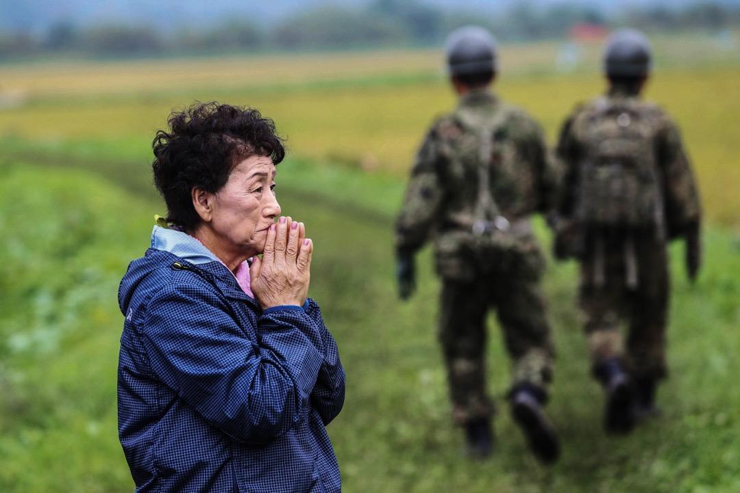 2018年9月8日,日本北海道,69歲婦人Tomoko Kinoshita在厚真町倒塌民房現場遠觀著搜救人員的工作,等候在地震後失蹤的姨姨和表親的消息。