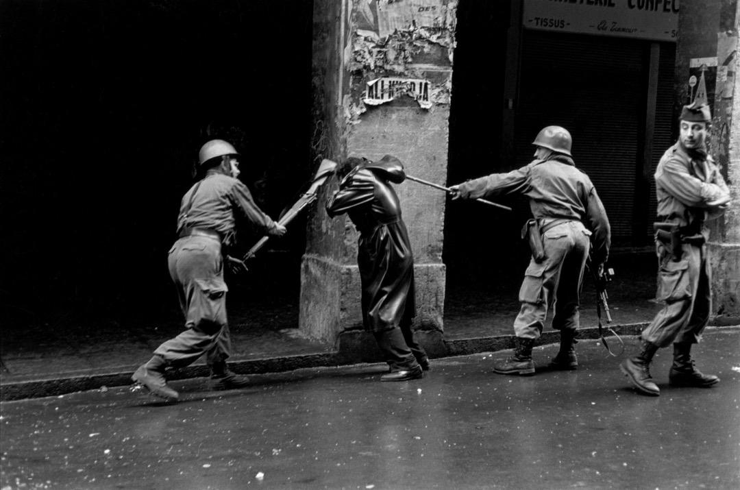 法軍在阿爾及爾犯下了戰爭罪行,這已是學界不爭的事實,根據阿戰專家Benjamin Stora的研究,拷打不僅是專門負責審問的保衛作戰隊的工作,在日常生活的街頭中,市民們也隨時會被施以暴行。圖為法軍在阿爾及爾暴力對待一名示威者。