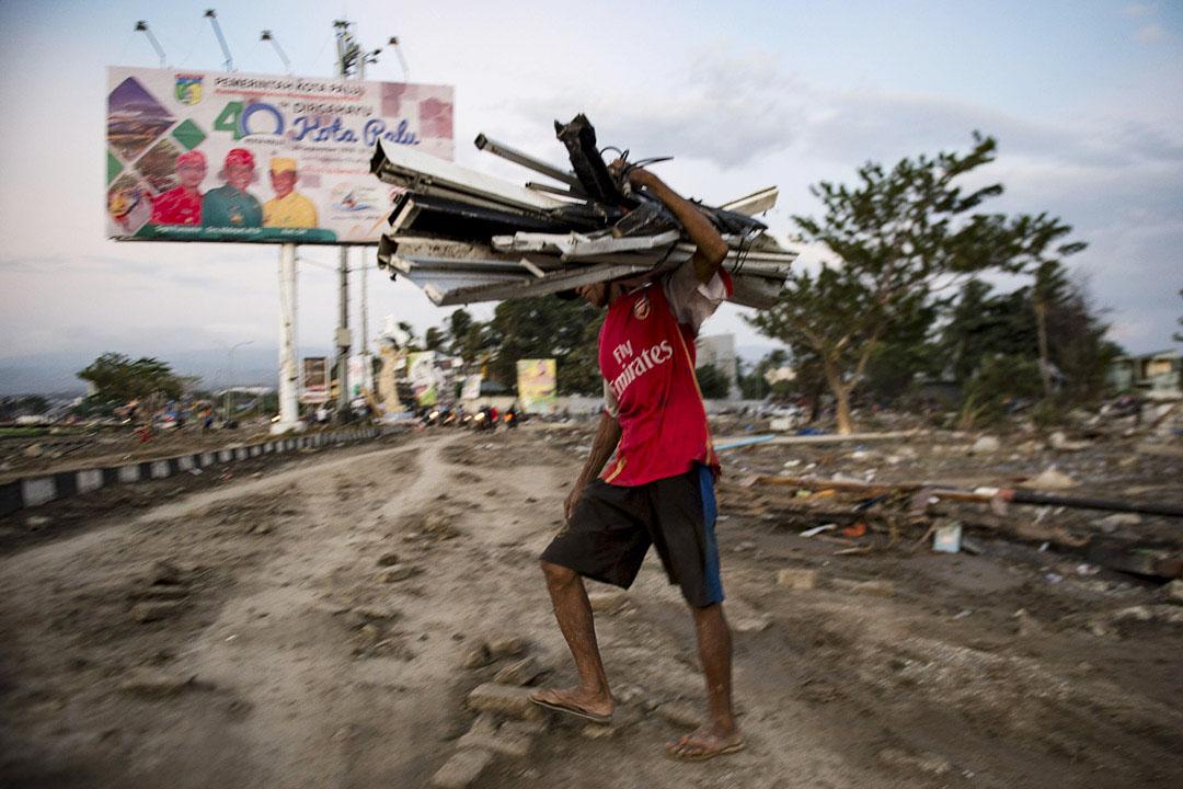 2018年9月29日,一名男子於遭受海嘯襲擊的海灘上收集有用物資。