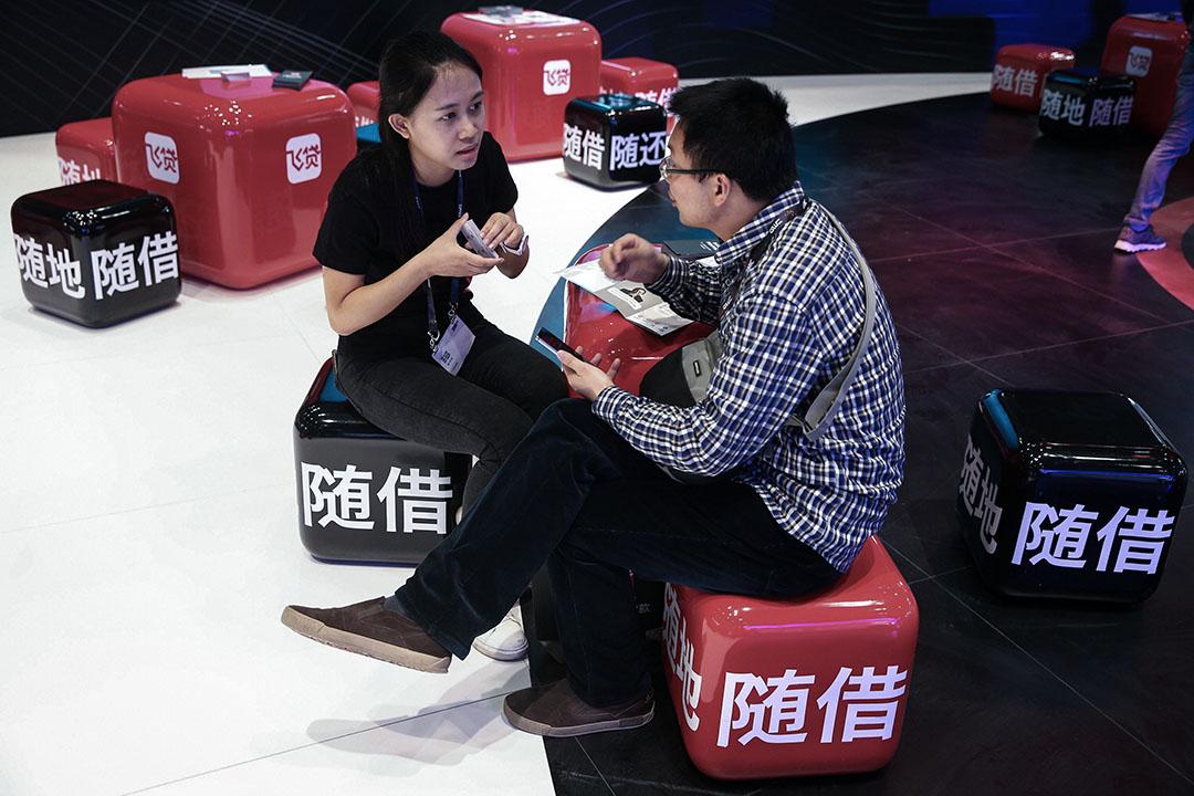 對P2P平台來說,只當信息中介,為「點對點」的借貸關係進行匹配效率太低,債權轉讓有利於它們批量生產業務,擴大經營。圖為2016年4月28日,中國北京2016年全球移動互聯網大會(GMIC),訪客與P2P金融公司人員對話。