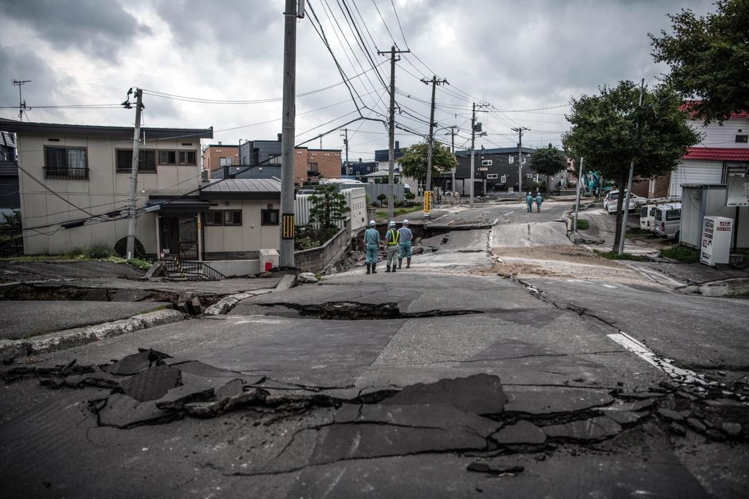 2018年9月7日,日本札幌清田區,道路在地震中嚴重損毀,數名維修人員在場觀察情況。