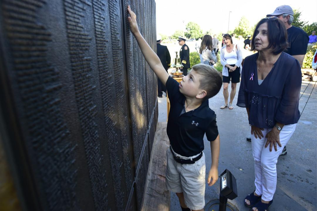 2018年9月11日,科羅拉多男孩 Will Faughnan 在9/11紀念館悼念他的叔叔 Chris Faughnan 在17年前的恐怖襲擊中於世貿中心工作時遇難。 攝:Paul Aiken/Getty Images