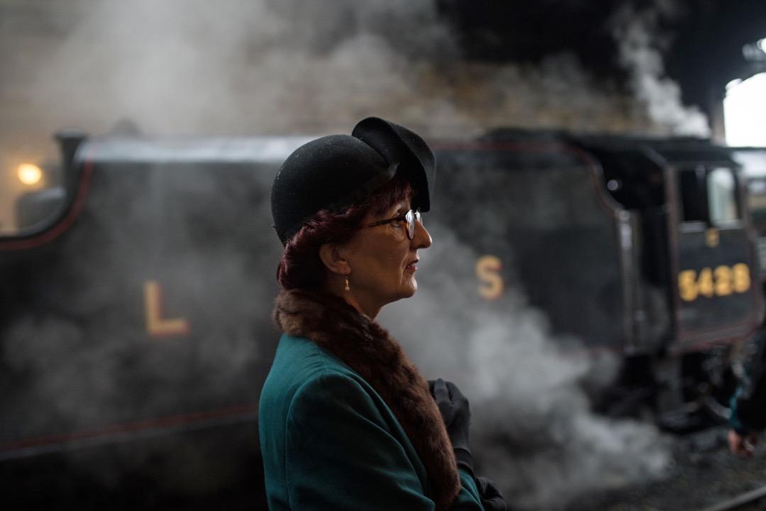 一名婦女站在蒸汽火車前。
