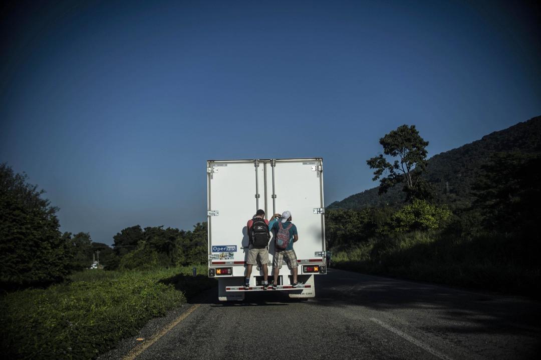 2018年10月25日,兩名洪都拉斯移民在墨西哥恰帕斯州城鎮Mapastepec的一條公路上,跳上了一輛往北行的貨車車尾。