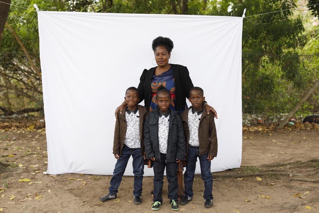 43歲的Nomathandazo Madlala和她的三胞胎兒子站在白布前。