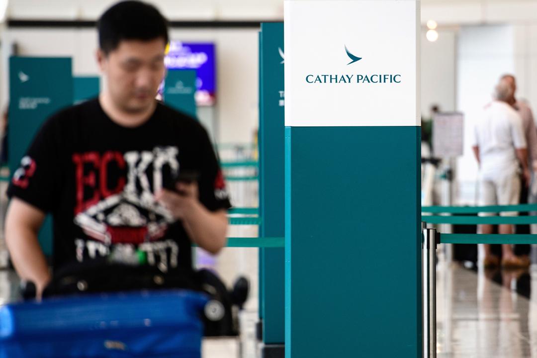 國泰航空證實今年5月初確認約940萬位乘客的個人資料被「未獲授權取覽」。圖為2018年8月7日在香港國際機場,一名旅客經過國泰辦理登機櫃枱。 攝:Anthony Wallace / AFP / Getty Images