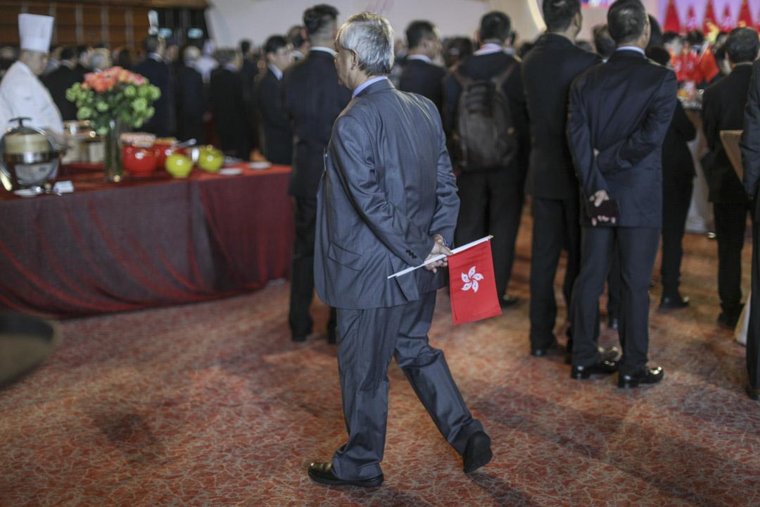 灣仔會展舉行國慶酒會,一名參加者手持香港及中國國旗進場。