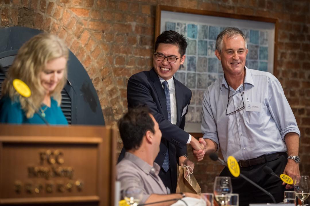 今年8月14日,香港外國記者會(FCC)邀請「香港民族黨」召集人陳浩天(中)出席講座,講座由 FCC 第一副主席 Victor Mallet(右)主持。圖為講座現場,陳浩天與 Victor Mallet 握手。 攝:Paul Yeung/Bloomberg via Getty Images