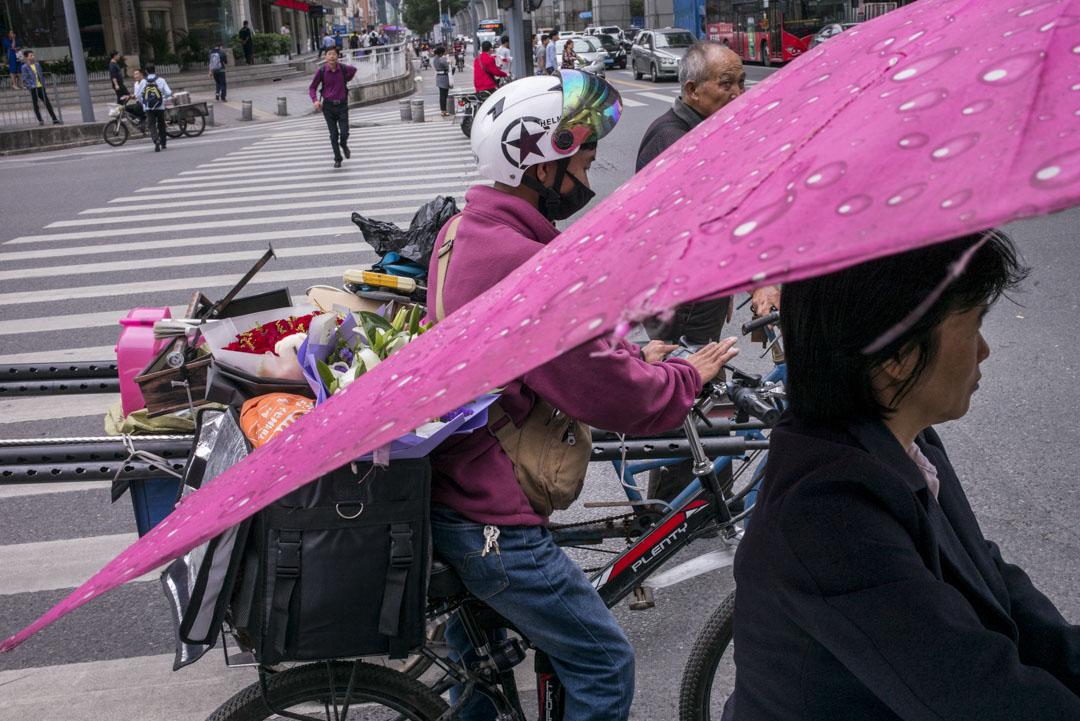 中國大肆鼓吹「消費升級」的那幾年。淘寶「雙十一」購物狂歡節,在幾年內很快蔓延至其它網購平台,又從線上電商延伸到線下零售實體店。圖為一位外賣送花的送貨員。