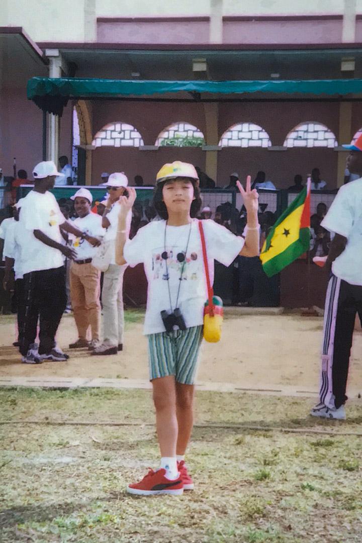 隨著黃峻昇的派令,黃子綪的幼年和青少年在非洲度過大半時光。圖為黃子綪參加聖多美普林西比當地活動,後方民眾手持聖多美國旗。