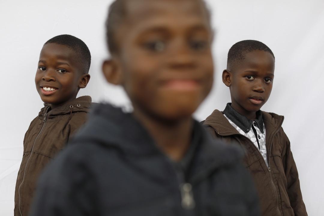 8歲三胞胎兄弟Simphiwe,Syamthende和Sneliswa微笑望向鏡頭。