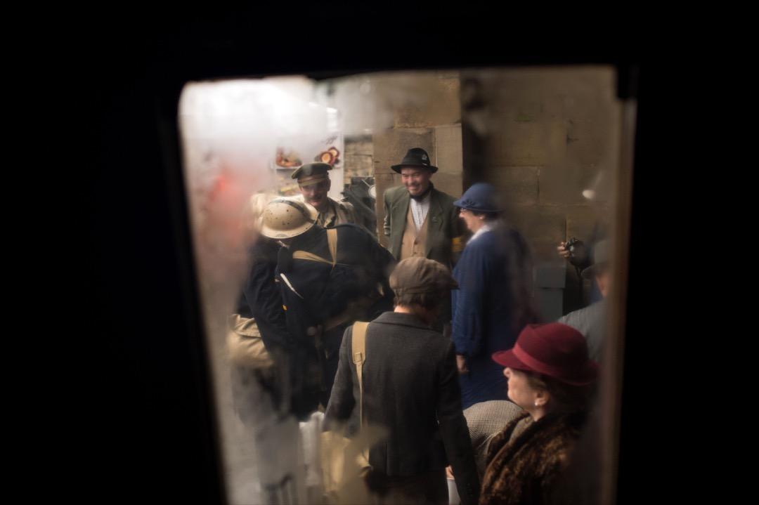 車窗鑲上一層薄薄的水蒸汽,而從窗內看到一班乘客在月台候車。