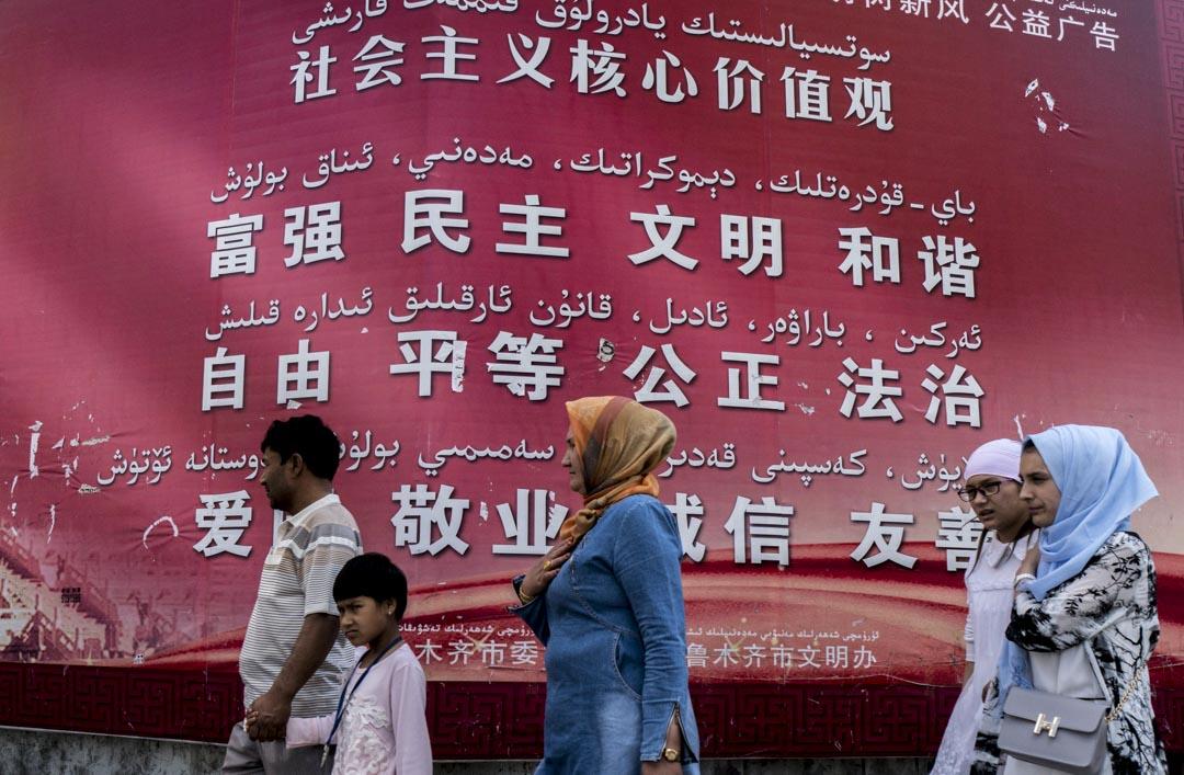 2016年6月18日,維吾爾族人走過一個巨大的廣告牌,牌上以漢語和維吾爾語寫下中國社會主義的核心價值觀。
