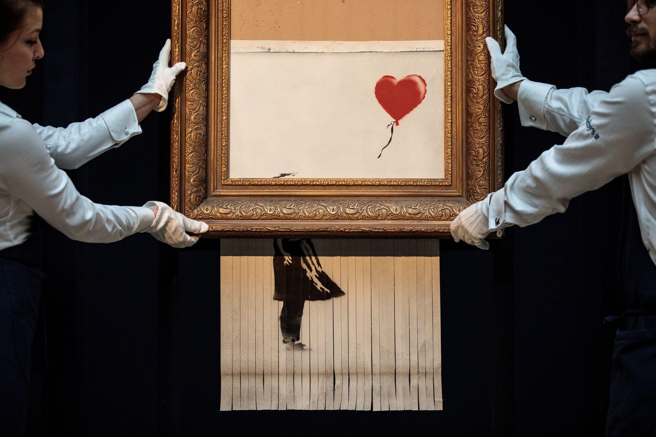2018年10月12日,英國倫敦蘇富比拍賣行,工作人員與英國塗鴉藝術家Banksy作品《愛在垃圾桶》(Love Is In the Bin)合照。