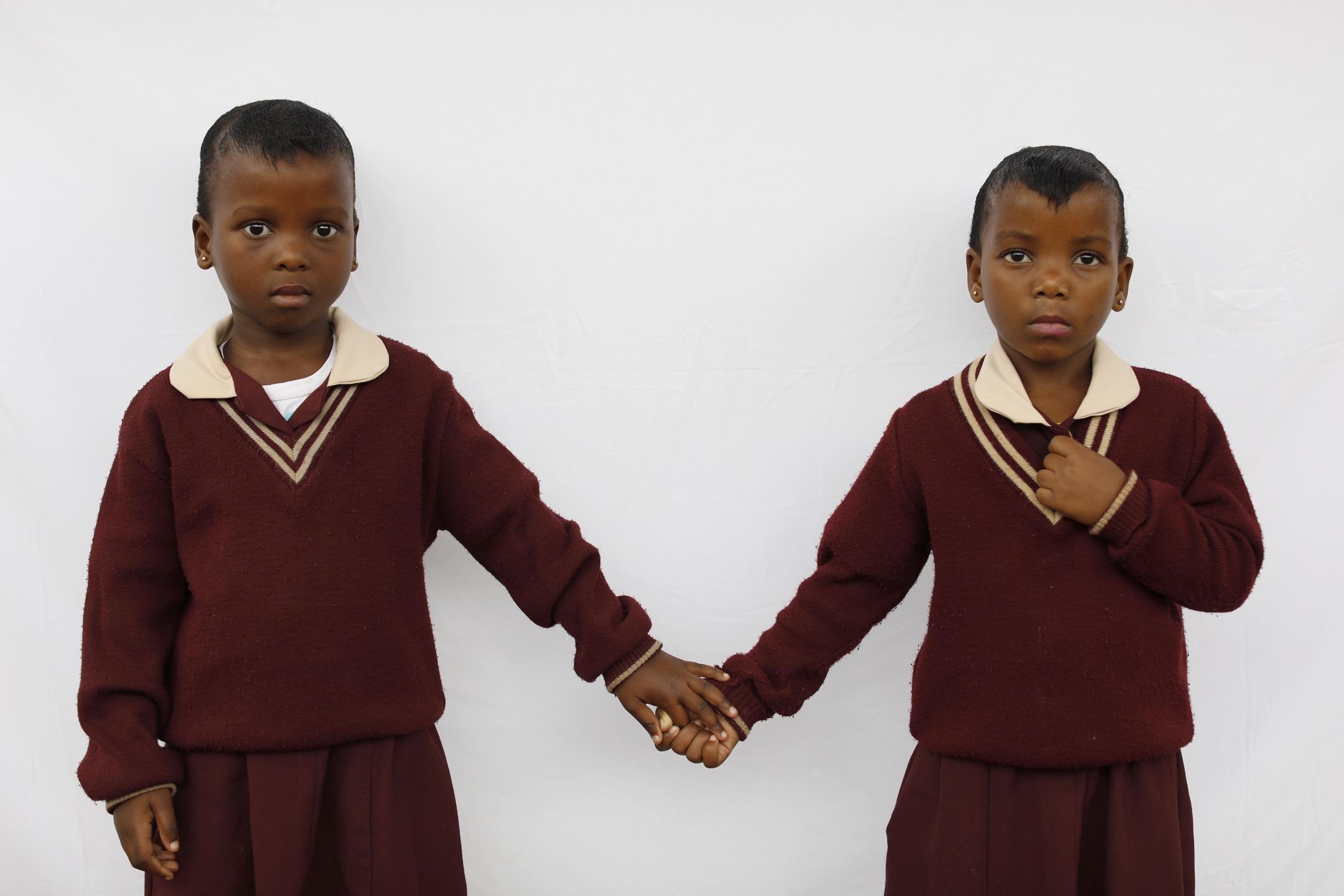 5歲雙胞胎Nomqebo和Nomkhosi牽起對方的手。 攝:Kim Ludbrook/EPA