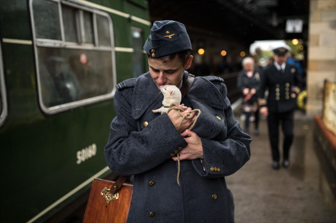 一名乘客抱著雪貂在月台行走。 攝:Oli Scarff /AFP/Getty Images