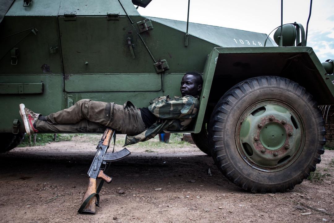 一名政府軍士兵在基地內的一輛裝甲車上休息。