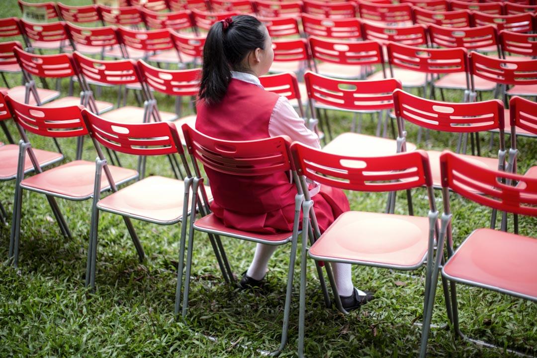 西區賀國慶嘉年華開始前,一名學生在觀眾席觀看預演。