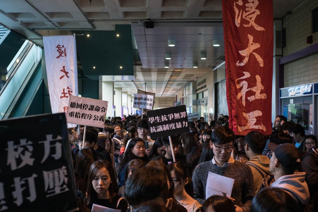 2018年1月26日,數百名浸會大學學生在校內遊行,抗議校方將兩名早前因佔領大學的語文中心反對普通話豁免試而被暫時停課的學生,批評校方無理處分。 攝:Stanley Leung/端傳媒