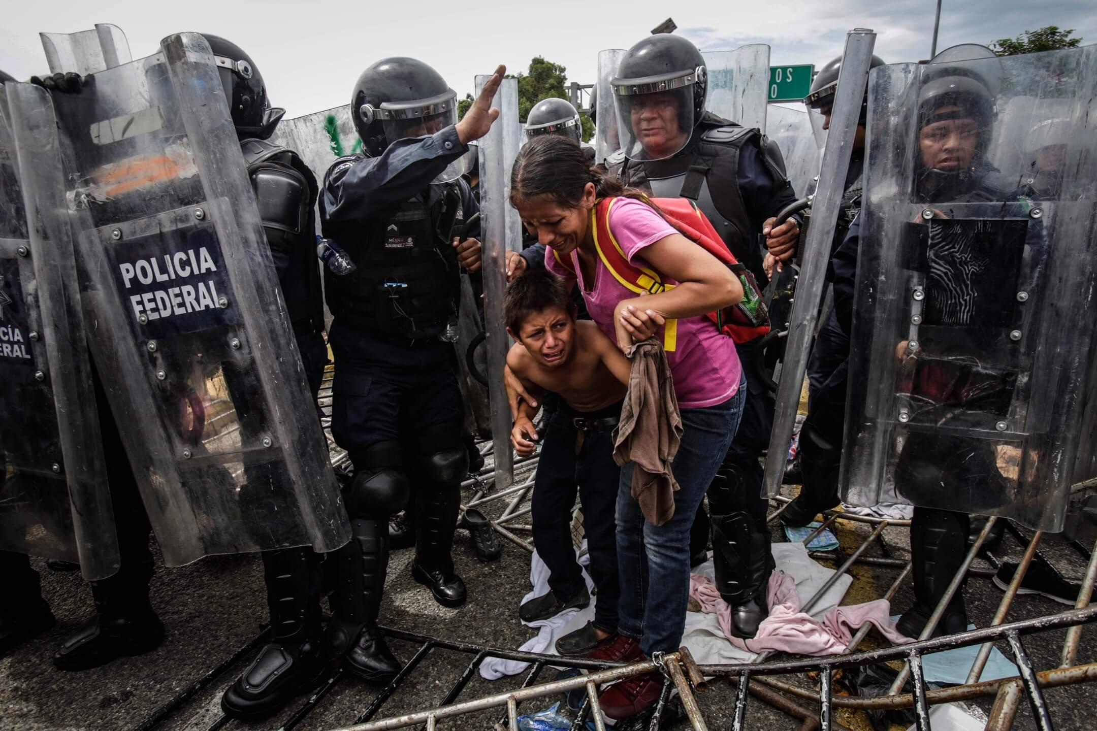 2018年10月19日,墨西哥伊達爾戈的邊防口岸,一對母子被防暴警察包圍,神色慌張。 攝:Moises Castillo/AP