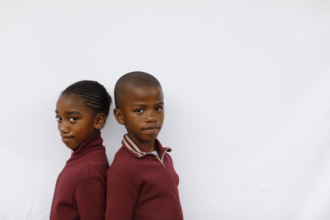 9歲雙胞胎Lyanda和Alwande背著對方站立。