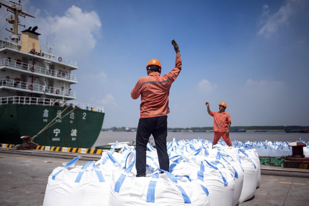 中美冷戰,早已開始。所謂冷戰,就是雙方都相信,自己的制度是優越的、自己的經濟體系是優越的,自己最終會在這場耐力比拼中勝出。圖為2018年8月,中國江蘇省張家港的工人在一個港口卸下一袋化學品。