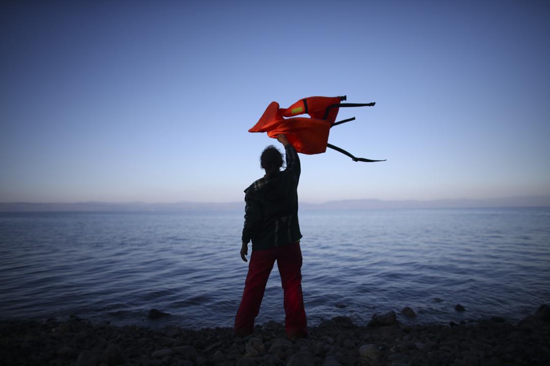 一名經土耳其來到希臘的難民,揮動救生衣指導一艘小船泊岸。 攝:Carl Court/Getty Images